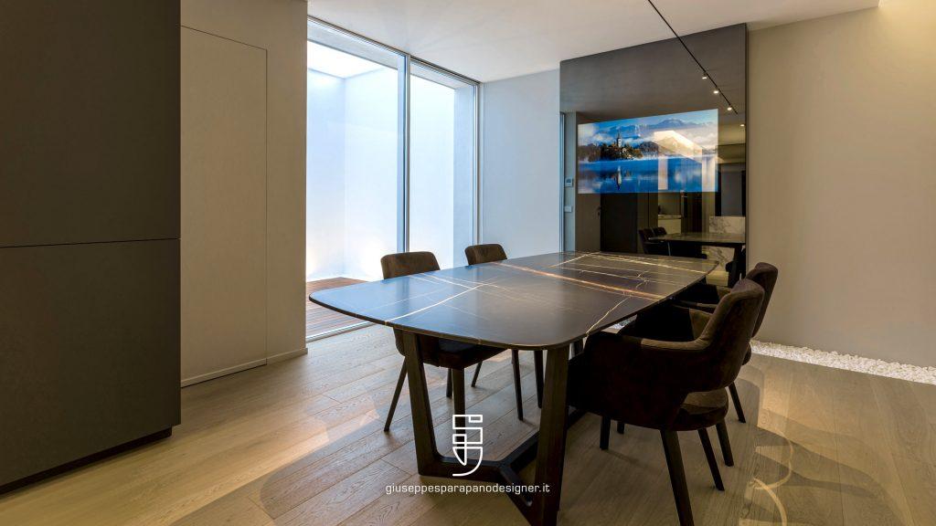 Zona pranzo con tavolo concorde marca Poliform con TV a scomparsa in parete a specchio