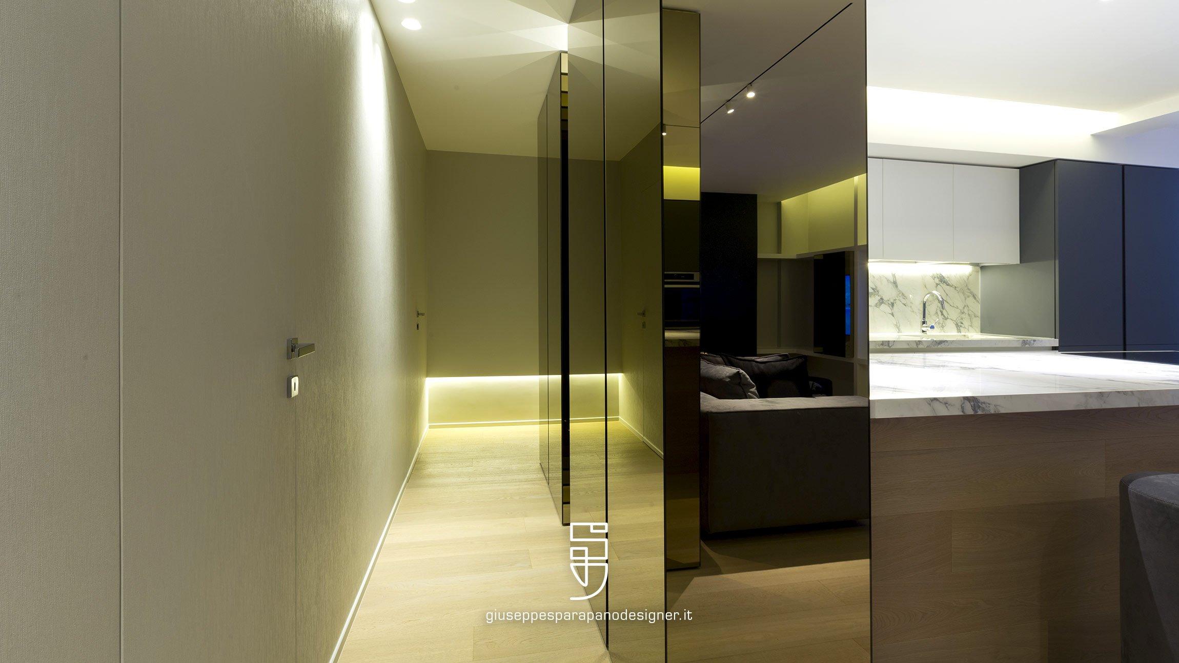 Corridoio con porte invisibili rivestito con carta da parati verniciabili e armadio rivestito a specchio e luci tecniche Viabizzuno