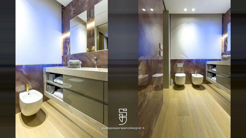 bagno con pareti in kerlite onice rosa, sanitari sospesi e rubinetti con finiture in oro satinato