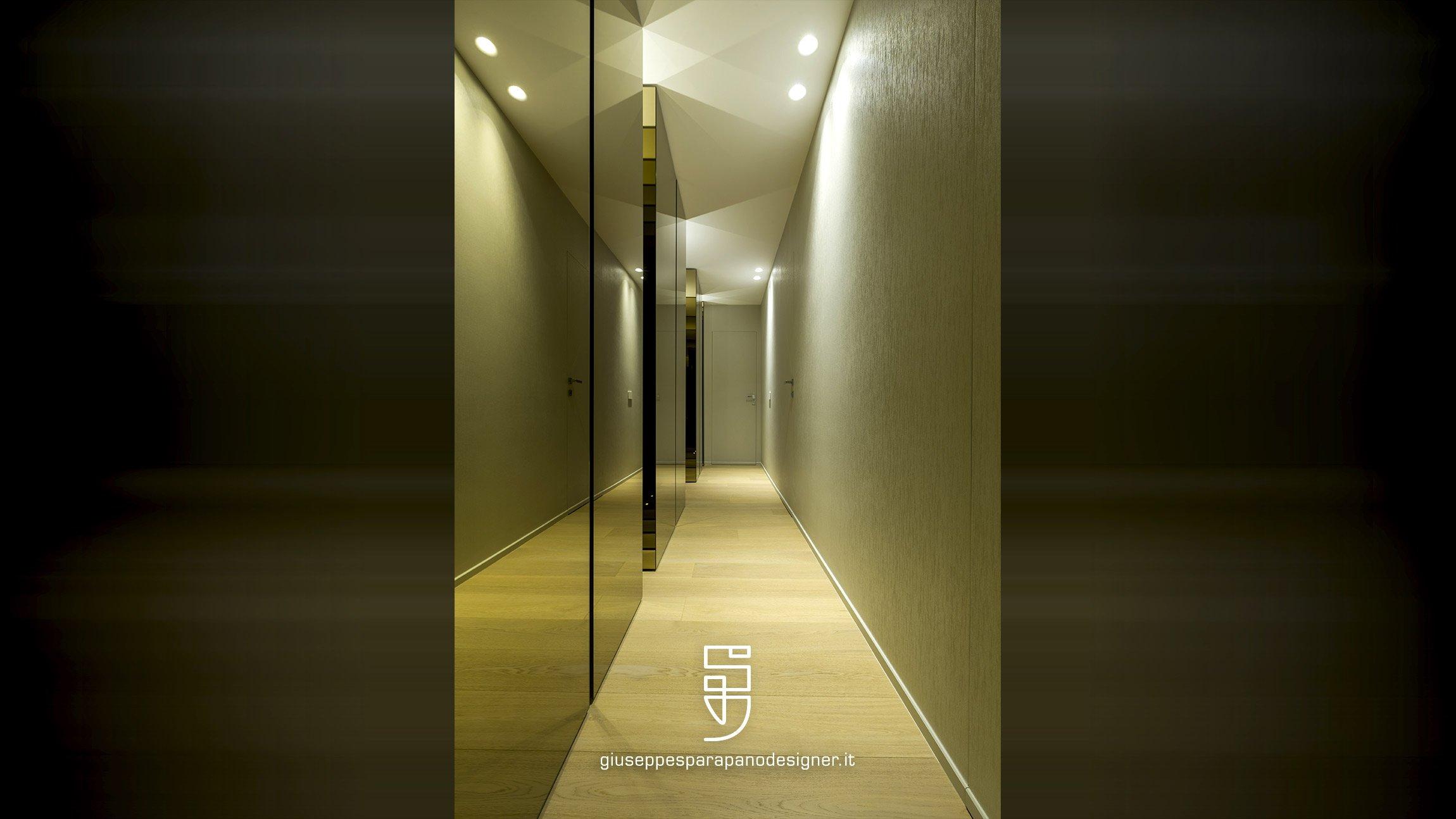 corridoio rivestito in carta da parati verniciabile su porta filomuro, luci led viabizzuno, armadi rivestiti a specchio e pavimento in rovere spazzolato naturale