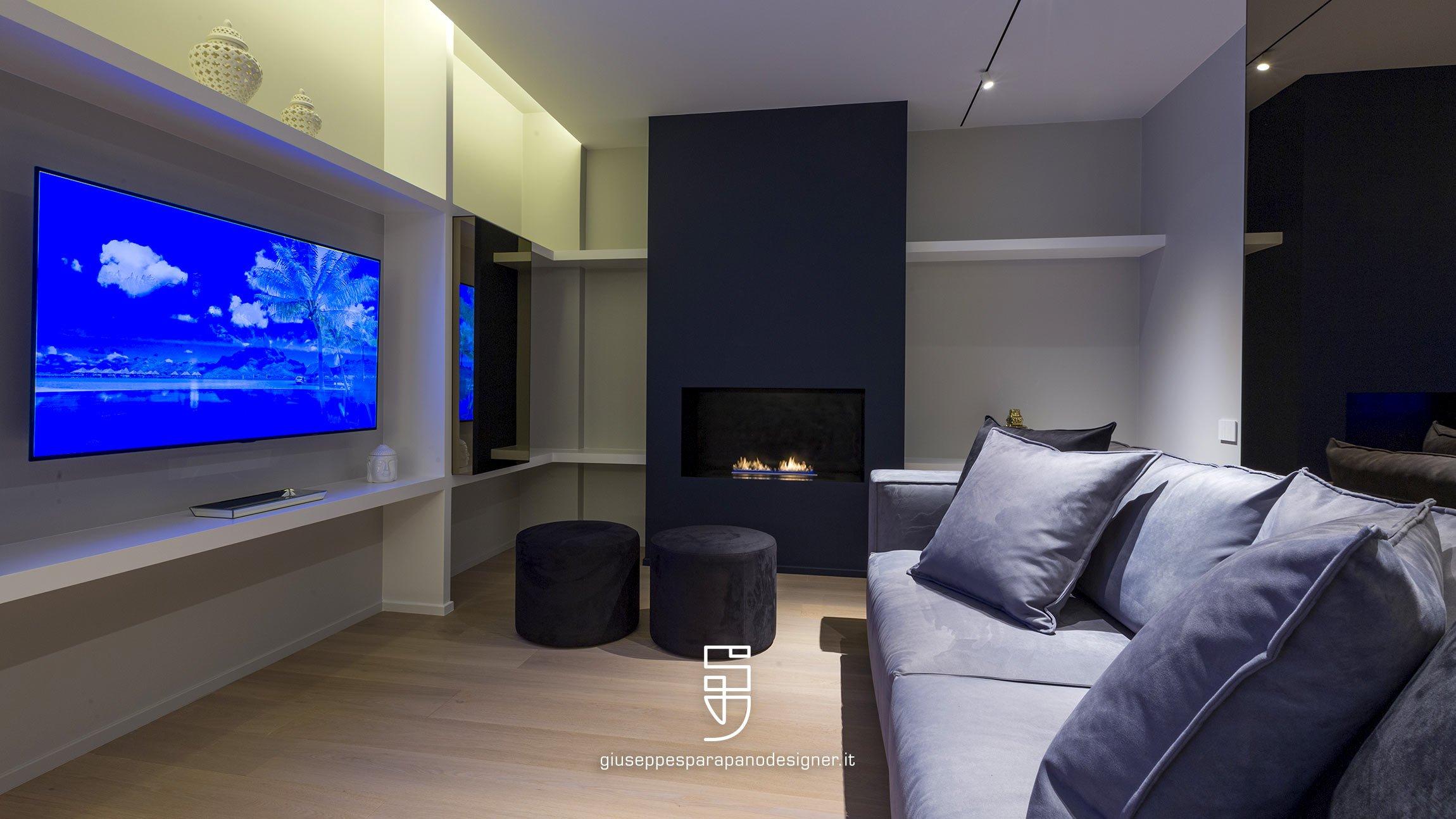 lounge con pavimento in parquet parete attrezzata con tv, divano e caminetto a bioetanolo